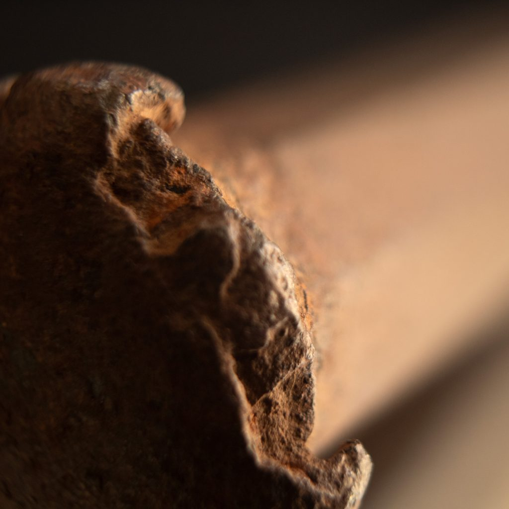 very close shot of the hammered end of an old splitting wedge.
